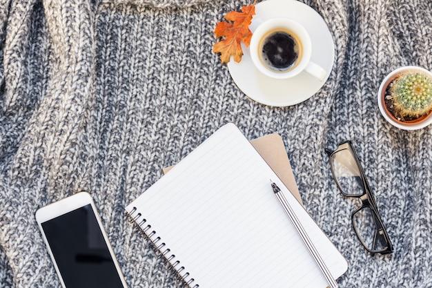 Lieu de travail à domicile avec une tasse de café sur un plaid tricoté