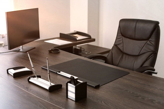 Lieu de travail du chef d'entreprise: fauteuil en cuir, instruments d'écriture, moniteur.