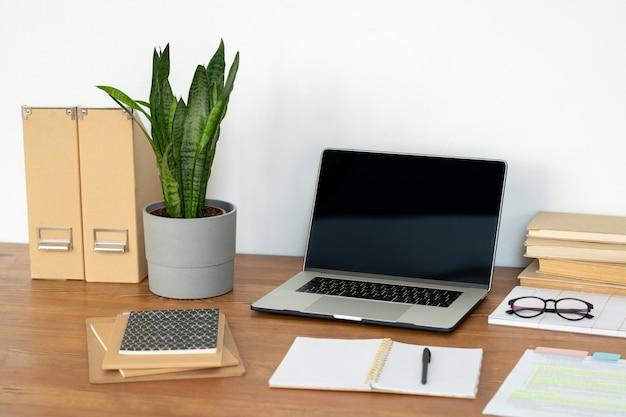 Lieu de travail du directeur de bureau ou d'un étudiant avec ordinateur portable, plante en pot, cahiers, livres et autres fournitures sur le bureau