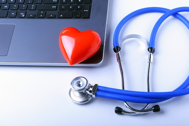 Lieu de travail du médecin avec stéthoscope, coeur rouge, ordinateur portable, prescription rx et cahier sur tableau blanc