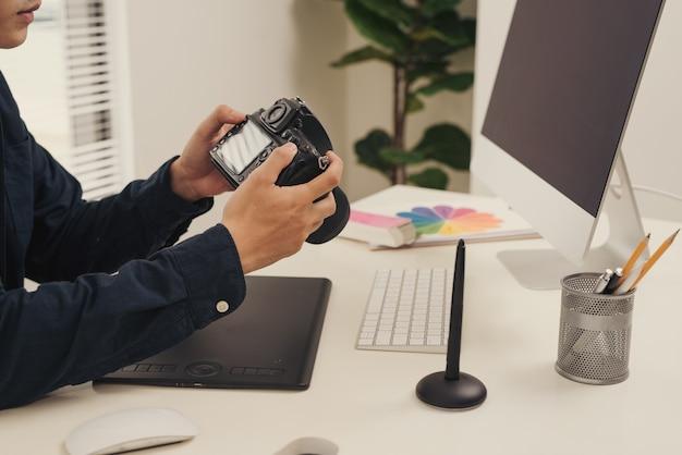 Lieu de travail du photographe. mains de concepteur créatif travaillant sur tablette graphique, équipement photographique sur table