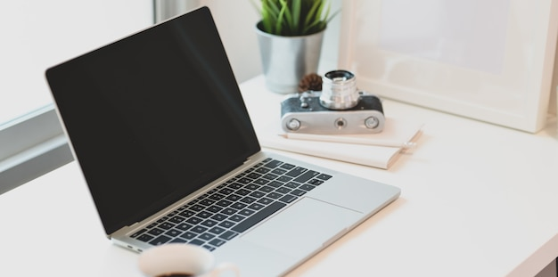 Lieu de travail du photographe moderne avec ordinateur portable ouvert