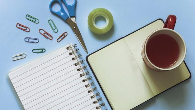 Lieu de travail élégant dans les couleurs bleues avec tasse et clips