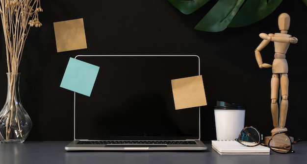 Lieu de travail élégant avec un ordinateur portable ouvert sur un bureau gris