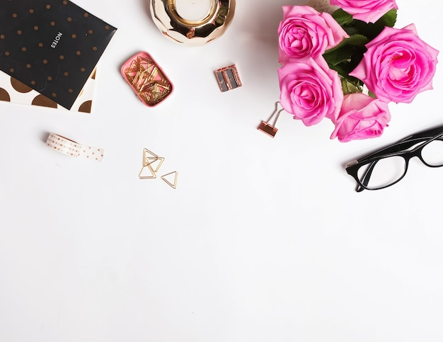 Lieu de travail élégant avec des roses roses et de petits accessoires sur fond blanc, vue de dessus