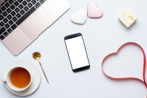 Lieu de travail féminin avec coeur rouge, ordinateur portable, téléphone mobile. concept de composition de saint valentin