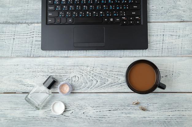 Lieu de travail de la femme avec ordinateur portable, tasse à café et produits de beauté