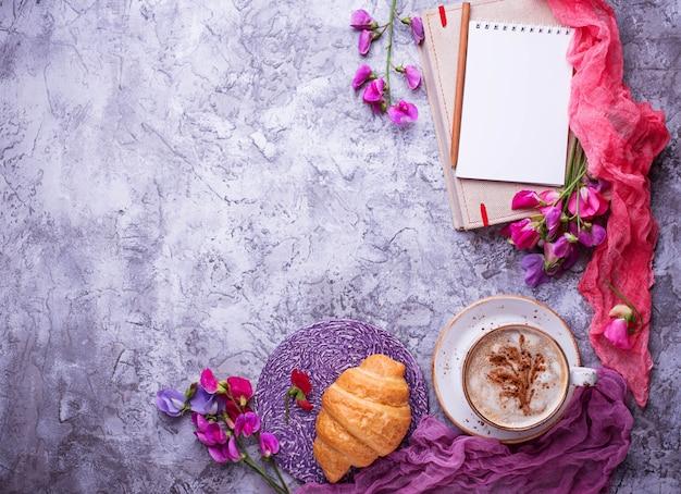 Lieu de travail des filles. café, croissants, fleurs et cahier. vue de dessus