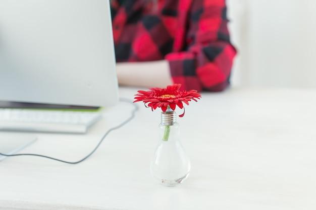 Lieu de travail avec fleur de gerbera et ordinateur. bureau à domicile minimaliste avec concepteur en arrière-plan