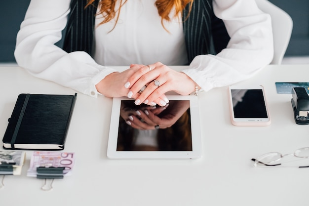 Lieu de travail de gestionnaire de médias sociaux. femme d'affaires. tablette, smartphone et fournitures de bureau
