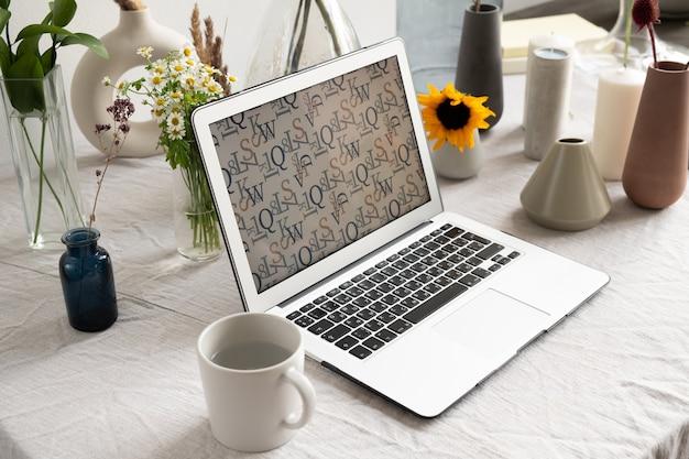 Lieu de travail d'homme d'affaires ou de designer créatif avec ordinateur portable et tasse avec de l'eau entourée de bougies et de vases avec des fleurs fraîches