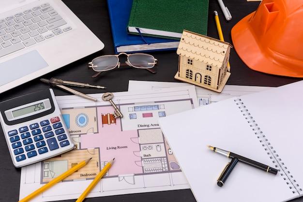 Lieu de travail de l'ingénieur avec ordinateur portable et plan de maison