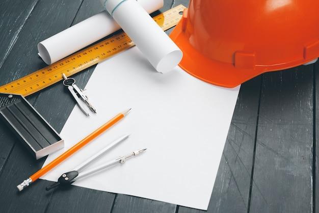 Lieu de travail d'ingénieur avec plans, boussole, crayon et casque de sécurité