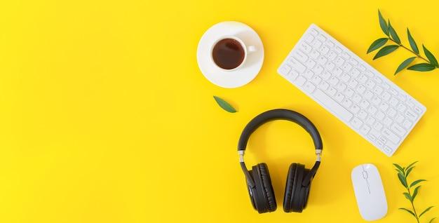 Lieu de travail jaune avec casque sans fil, clavier, souris, tasse à café