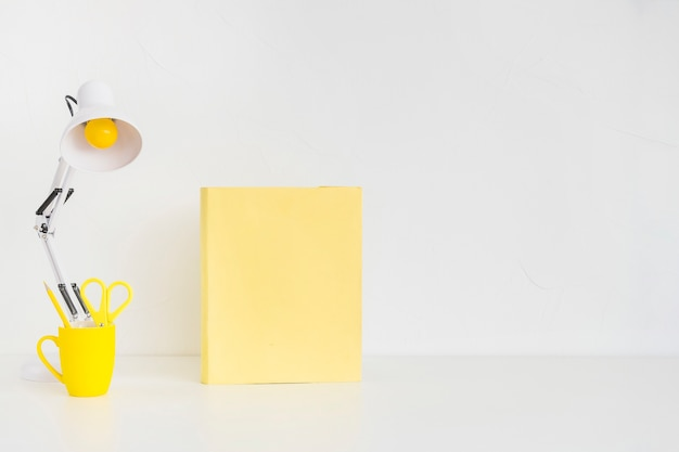 Lieu de travail avec lampe de lecture blanche et carnet jaune