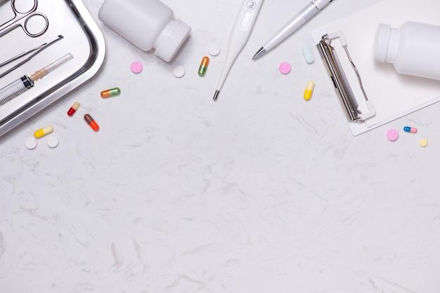 Lieu de travail d'un médecin. stéthoscope, presse-papiers, pilules et autres trucs sur le bureau.