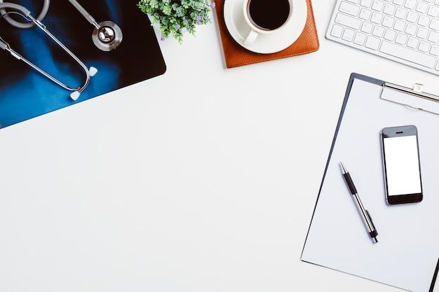 Lieu de travail médical avec stéthoscope, carnet, tasse de café, clavier et film radiographique sur