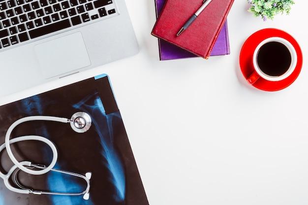 Lieu de travail médical avec stéthoscope, tasse de café, livre, ordinateur portable et film radiographique sur wh