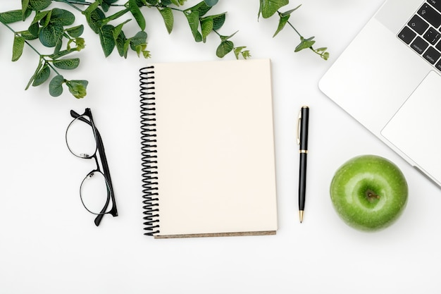 Lieu de travail minimal avec ordinateur portable et bloc-notes vierge