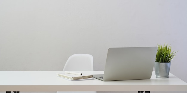 Lieu de travail minimal avec un ordinateur portable et des décorations sur une table en bois blanche