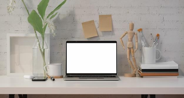 Lieu de travail minimal avec un ordinateur portable à écran blanc ouvert