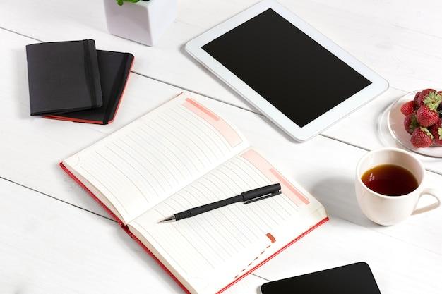 Lieu de travail minimaliste élégant avec tablette et ordinateur portable et lunettes sur fond blanc de style plat