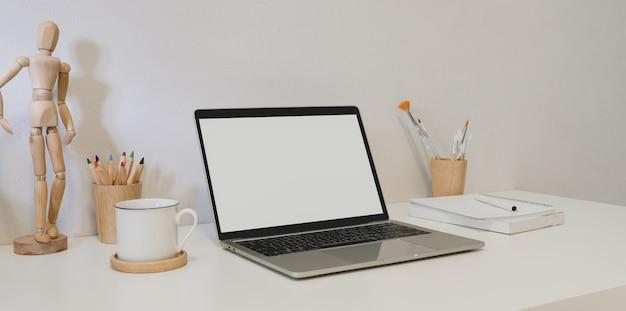 Lieu de travail minimaliste avec ordinateur portable à écran blanc
