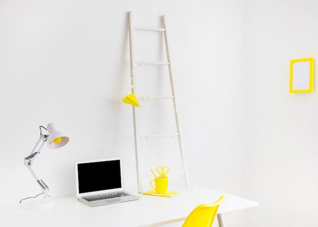 Lieu de travail moderne en couleurs blanches et jaunes avec cadre photo