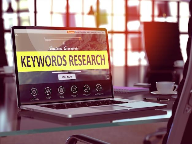 Lieu de travail moderne avec ordinateur portable montrant la page de destination avec des mots-clés researchconcept. image tonique avec mise au point sélective.