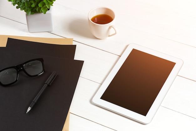 Lieu de travail moderne avec tablette numérique et téléphone portable tasse de stylo à café et feuille vide de ...
