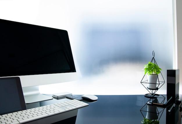Lieu de travail avec ordinateur moderne sur une table en verre, écran noir simulé, plante d'intérieur et fournitures.