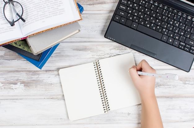 Lieu de travail avec ordinateur portable, bloc-notes, stylo et livres