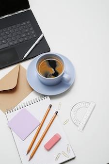 Lieu de travail avec ordinateur portable, café et bloc-notes, vue de dessus, copyspace