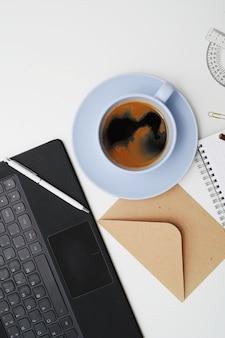 Lieu de travail avec ordinateur portable, café et bloc-notes, vue de dessus
