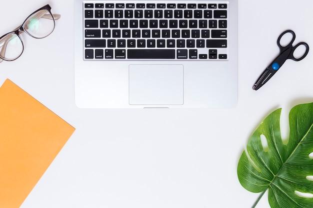 Lieu de travail avec ordinateur portable et ciseaux