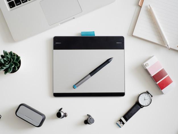 Lieu de travail avec ordinateur portable, ordinateur portable, tablette graphique et smartphone.