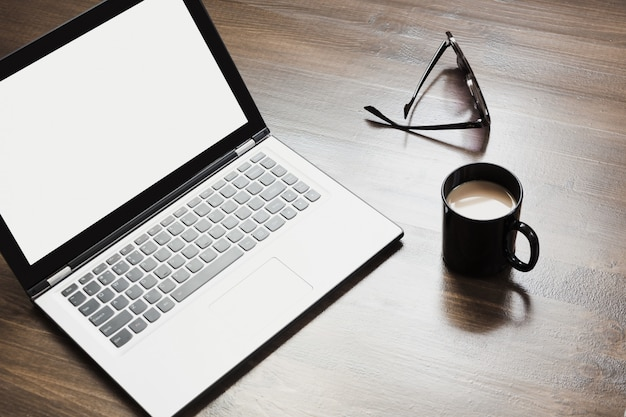 Lieu de travail avec ordinateur portable ouvert, café et accessoire sur la table de bureau.