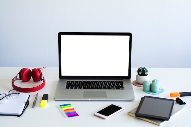 Lieu de travail avec ordinateur portable près de smartphone, tablette, ordinateur portable et casque