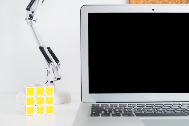 Lieu de travail avec ordinateur portable et rubik's cube