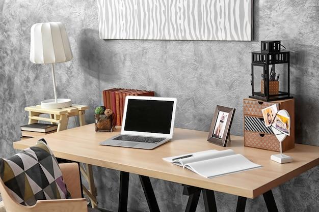 Lieu de travail avec ordinateur portable sur table dans une chambre moderne