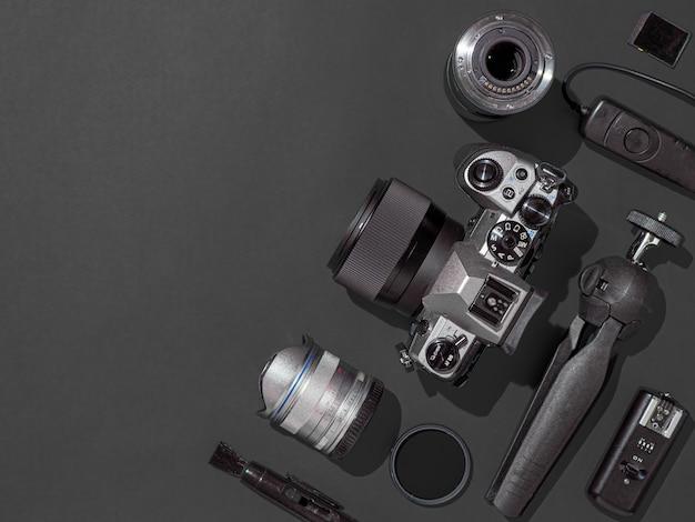Lieu de travail de photographe avec appareil photo reflex numérique, objectif, tablette à stylet et accessoires d'appareil photo sur fond noir. appareil photo, photographie, concept de contenu visuel. mise à plat ou vue de dessus. copiez l'espace. lumière forte.