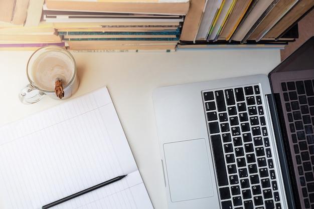 Lieu de travail plat laïque avec livres, cahier, crayon, café et ordinateur. e-learning