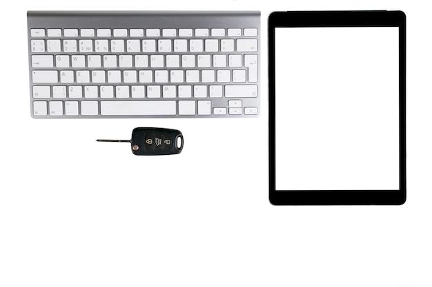 Lieu de travail professionnel avec clavier sans fil, tablette, ordinateur portable de souris et clés de voiture sur fond blanc. bureau avec espace de copie. espace vide pour le texte