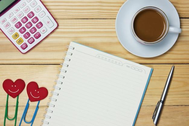 Lieu de travail simple avec une tasse de café, du papier pour ordinateur portable, un stylo, un trombone et une calculatrice