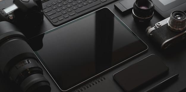 Lieu de travail sombre et branché avec des fournitures pour tablette, smartphone, appareil photo et bureau