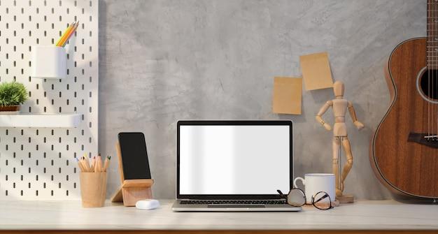 Lieu de travail de style loft avec un ordinateur portable à écran blanc