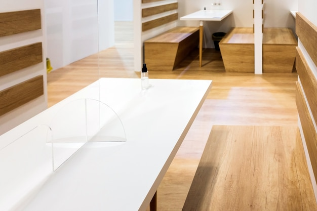 Lieu de travail vide, avec tables et chaises en bois, avec cloisons en plastique transparent pour tenir des réunions.