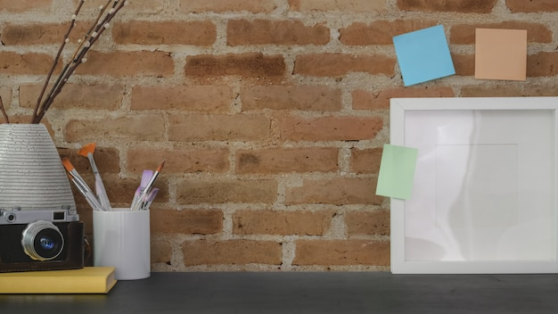 Lieu de travail vintage avec cadre maquette, fournitures de bureau et espace de copie avec mur de briques