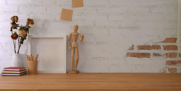 Lieu de travail vintage avec cadre maquette et fournitures de bureau sur table en bois et mur de briques