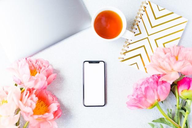 Lieu de travail, vue du bureau. ordinateur portable, pivoine rose, tasse de thé et téléphone portable. espace de travail de la femme.